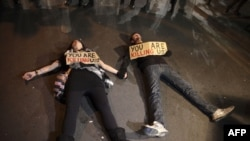 Cypriot protestors lie on the ground with signs during a demonstration against an EU bailout deal outside the parliament in the capital, Nicosia, on March 19.
