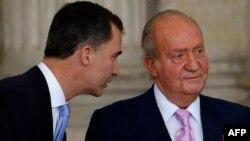 Испанияның бұрынғы королі бірінші Хуан Карлос (оң жақта) пен оның мұрагер ұлы Фелипе. Мадрид, 18 маусым 2014 жыл.