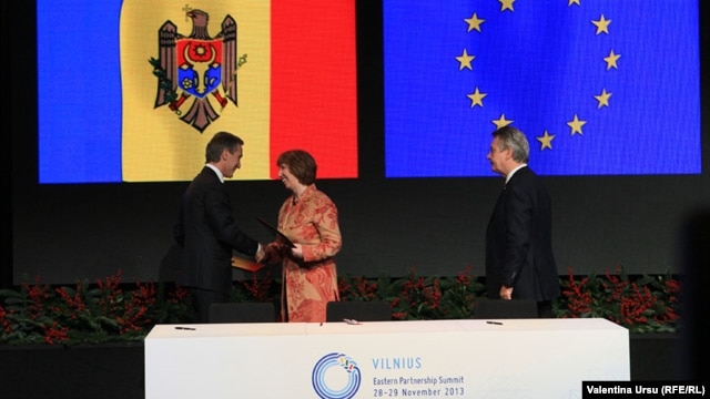 Moldovan Prime Minister Iurie Leanca (left) shakes hands with EU foreign policy chief Catherine Ashton as European Commissioner for Trade Karel de Gucht looks on after Leanca initialed Moldova's Association Agreement with the EU.