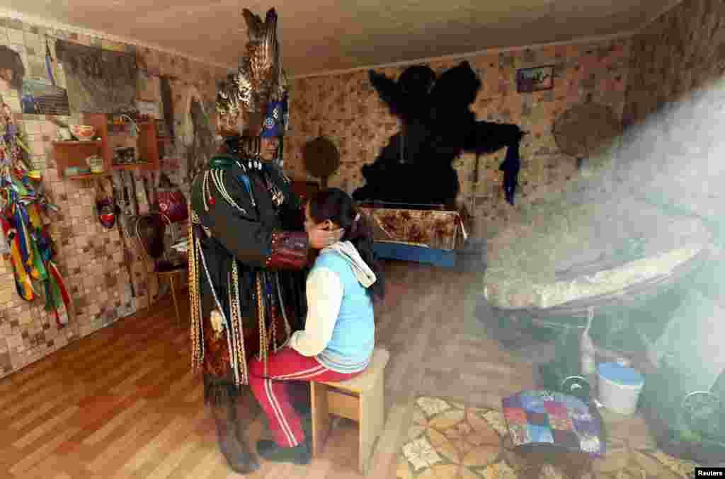 Шаманами становятся не только мужчины. Этнографы и вовсе утверждают, что первыми шаманами были именно женщины. На фото — Саида Монгуш, женщина-шаман, которая пытается исцелить девятилетнюю девочку от врожденного искривления позвоночника.