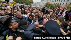 Opposition supporters clash with police in front of the Tbilisi city council during a protest rally in Tbilisi on October 10.