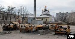 Burned cars are seen after shelling near a church in the southeastern city of Mariupol on February 25.