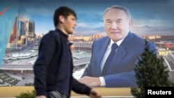 A man walks past an election banner of Kazakh President Nursultan Nazarbaev in Almaty.