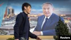 A man walks past an election banner of Kazakh President Nursultan Nazarbaev in Almaty.