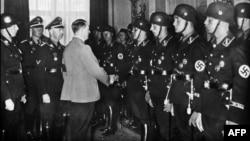 Канцлер Німеччини Адольф Гітлер (у цивільному) потискає руки молодим бійцям елітного підрозділу СС. Третій зліва – керівник гестапо Генріх Гіммлер. Берлін, 1937 рік (ілюстраційне фото)