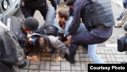 "Полиция 18 августта ""Сазлык мәйданы"" эшендә гаепләнүчеләргә төрмә җәзасы чыгарган мәхкәмә янына җыелганнарны тоткарлый. Илдар Дадин зәңгәр футболка һәм зәңгәр чалбар кигән, ул сул якта."