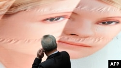 A member of the Ukrainian parliament looks at a giant placard on April 25 depicting former Prime Minister Yulia Tymoshenko set by the opposition in the parliament's sitting hall.
