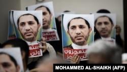 هواداران شیخ علی سلمان، رهبر جمعیت وفاق، در یک تجمع اعتراضی تصاویری از او را بر سر دست دارند.