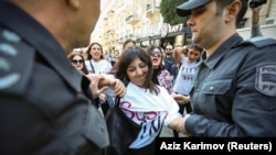 A women's rights protester is detained by police in Baku on October 20.