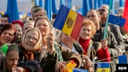 Moldovans wave flags as they attend a pro-European rally in Chisinau late last year.