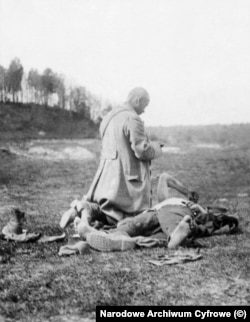 A priest tends to a dying Polish soldier.