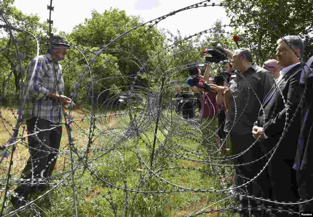 Georgian President Giorgi Margvelashvili (second right) and his Ukrainian counterpart Petro Poroshenko (right) speak with a local resident as they visit the line of control with the breakaway region of South Ossetia on July 19. (Reuters/Irakli Gedenidze)