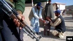 Пакистанский сотрудник сил безопасности и медики у места вакцинации против полиомелита. Иллюстративное фото.