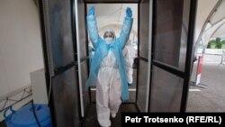 Медицинский работник проходит через дезинфекционный тоннель в пункте сдачи анализов на коронавирус. Алматы, 14 мая 2020 года.