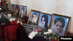 Armenia - Flowers are put by the pictures of six members of an Armenian family murdered in Gyumri during their funeral, 15Jan2015.