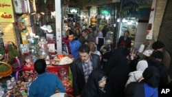 "In this Wednesday, March 13, 2019 photo, people shop ahead of the Iranian New Year, or Nowruz, meaning ""New Day"" at the Tajrish traditional bazaar in northern Tehran, Iran. The holiday, dating back to at least 1700 B.C. and ancient Zoroastrian traditions,"