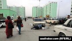 Женщины на улице проходят мимо мужчины, моющего машину. Агшабат, 27 марта 2013 года.