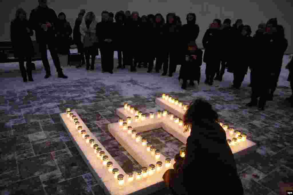 Commemorating the victims of a Soviet crackdown on independence protesters in Lithuania on January 13, 1991, people place lit candles outside the Ministry of Education and Science in Vilnius. (epa)