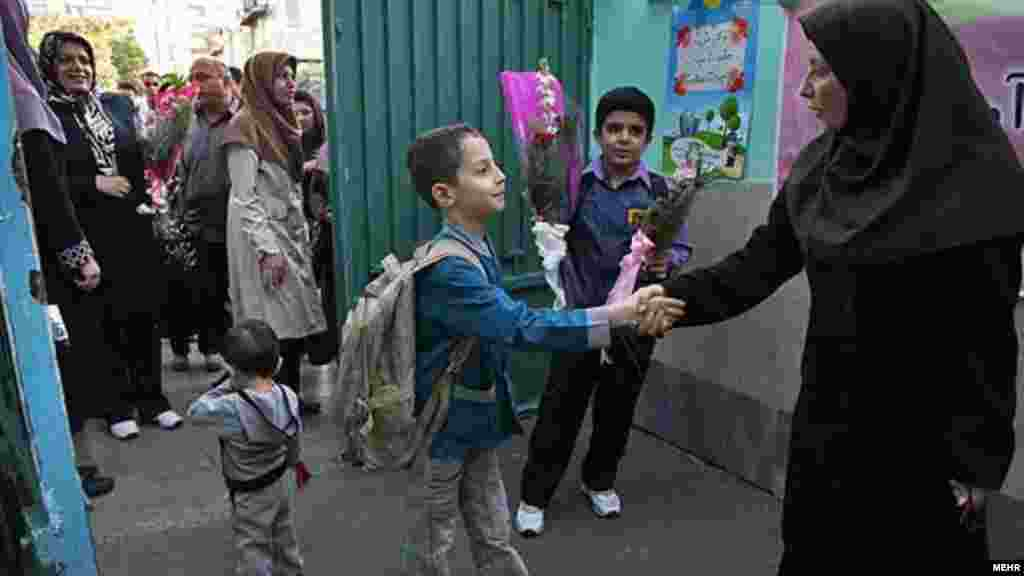 A pupil shakes hands with a teacher in Iran.