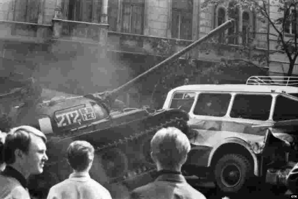 A Soviet tank rams a city bus after protesters set up a barricade to block Soviet forces near the Czechoslovak radio headquarters.