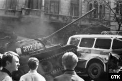 Советский танк прорывается сквозь баррикады, установленные жителями Праги возле здания Чехословацкого радио, 21 августа 1968 года