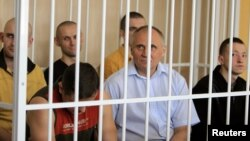 Belarus -- Former presidential candidate V Statkevich (C, first row) sits in a guarded cage during a court hearings in Minsk, 26May2011