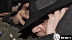 Galliano is surrounded by officers as he leaves a police station in Paris in February 2011.