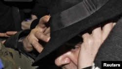 Британский модельер Джон Гальяно в сопровождении полицейских выходит из полицейского участка.Париж, 28 февраля 2011 года.