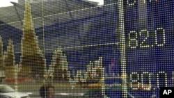 Човек поминува покрај електронска табла што го прикажува курсот на јенот во однос на доларот во Токио на 3 август 2011 година.