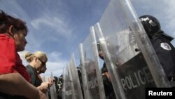 Protesters face a police barricade in front of a government building in Pristina on October 17.