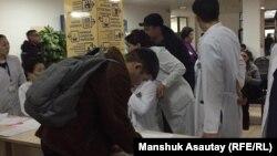 Зардап шеккендердің тізімінен туысын іздеп жатқан адам. Алматы қалалық № 4 клиникалық ауруханасы.