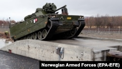 A Norwegian CV9030 armored infantry combat vehicle drives up a ramp and on to a train during thee NATO-led Trident Juncture exercises in Stjordal, Norway, on October 24.