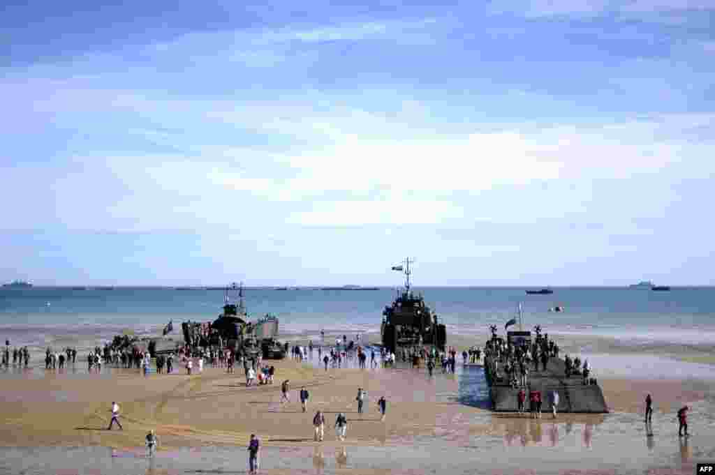 People walk aboard ships set up on the beach in Arromanches prior to a joint French-Dutch D-Day commemoration ceremony on June 6, 2014.