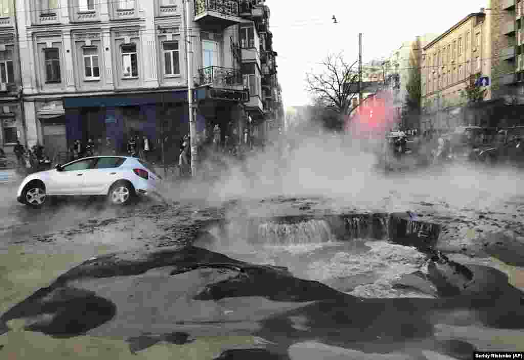 A car falls down in a hole caused by burst heating pipe in the center of the Ukrainian capital, Kyiv, on November 5. (AP/Sergey Ristenko)