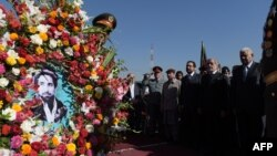 Afghan Chief Executive Officer Abdullah Abdullah (second right) watches as a soldier carries a wreath with a photo of slain Afghan national hero Ahmad Shah Masud during an event marking the 15th anniversary of his death on September 8 in Kabul.