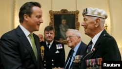British Prime Minister David Cameron (left) meets Arctic Convoy veterans during a special medal presentation ceremony on Downing Street on March 19.