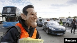 A striking refinery worker, wearing a mask of French President Nicolas Sarkozy, distributes leaflets to drivers during a protest against pension reform at a toll booth near Vienne on October 22.