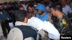 یکی از ساکنان حوله جسدی را به یکی از ناظران سازمان ملل نشان می دهد