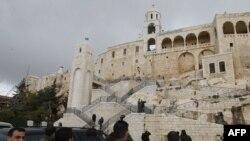 Gazetarët e përcjellur nga policia, në organizim të qeverisë së Sirisë, i shohin dëmet në një objekt fetar