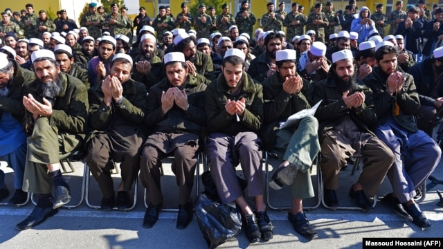 Released Taliban prisoners sit on chairs and pray during a ceremony in Pul-e Charkhi jail on January 4. Observers wonder how many of them will simply rejoin the fight?