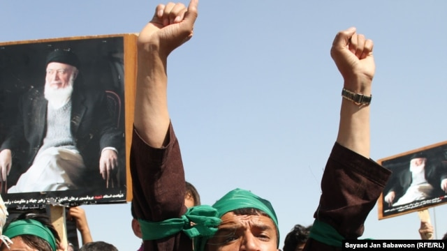 Supporters of slain former Afghan President Burhanuddin Rabbani shout slogans and hold up his portrait during a protest against the Taliban and Pakistan in Kabul on September 27.