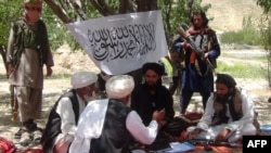 Taliban fighters with talk with villagers in near Gardez, the capital of Paktia province on July 18.