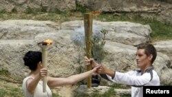 Греческая актриса Ино Менегаки зажгла огонь Олимпиады-2012 от лучей солнца и передала его первому факелоносцу – пловцу Спиросу Янниотису. Олимпия, Греция, 10 мая 2012 г