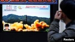 Түндүк Корея ракета учурганы тууралуу кабарды Токионун тургундары көчөдөгү экрандан көрүп жатышат. 29-ноябрь, 2017-жыл.