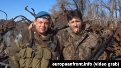 Сербський бойовик Деян Берич передає «привіт» уряду Сербії (справа)