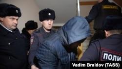 Одного из полицейских, обвиненных в изнасиловании коллеги, сопровождают в суд