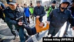 Полицейские тащат одного из участников акции протеста в Баку. 10 марта 2013 года.