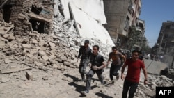 Syrians run for cover during reported government air strikes in the rebel-held town of Douma, east of the capital Damascus late last week.
