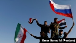 Syrians wave Iranian, Russian, and Syrian flags during a protest against U.S.-led air strikes in Damascus last month.