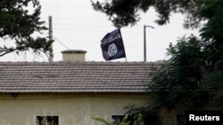 An Islamic State flag flies over the custom office of Syria's Jarablus border gate as it is pictured from the Turkish town of Karkamis. (file photo)